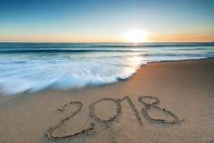 meddelande som 2018 är skriftligt i sanden Arkivbild