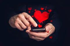 Meddelanden för text för manmaskinskrivningförälskelse på en smartphone för valentin da Royaltyfri Fotografi
