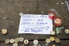 Meddelanden, stearinljus och blommor i minnesmärken för offren Arkivfoto