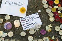 Meddelanden, stearinljus och blommor i minnesmärken för offren Fotografering för Bildbyråer