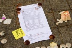 Meddelanden, stearinljus och blommor i minnesmärken för offren Arkivbild