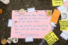 Meddelanden, stearinljus och blommor i minnesmärken för offren Arkivbilder