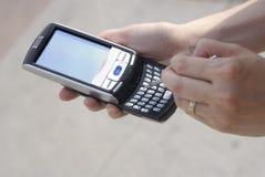 meddelandepdatelefon som texting Arkivfoto