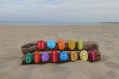 Meddelandet för den lyckliga födelsedagen med en idérik sammansättning av färgat stenar bokstäver på stranden arkivfoton