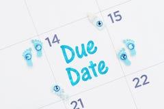 Meddelandet för det förfallna datumet på en månatlig kalender med mycket litet behandla som ett barn fotspår, flaskan och pladder royaltyfri bild