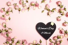 Meddelandet för hälsningen för dagen för kvinna` s på hjärta-svart tavla med litet torkar arkivbilder