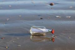 Meddelandet i flaska tvättade sig på sanden Royaltyfri Fotografi