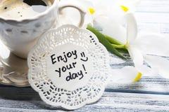 Meddelandet tycker om din dag med koppen kaffe och härliga blommor Royaltyfri Foto