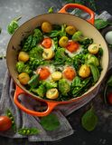 One Pan Green shakshuka with kale, broccoli, sweet peas, spinach and dill with free range eggs, perfect supper. Stock Photo