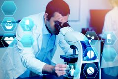 Composite image of medecine. Medecine against science student looking through microscope Royalty Free Stock Image