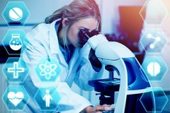 Composite image of medecine. Medecine against science student looking through microscope in the lab Stock Photo