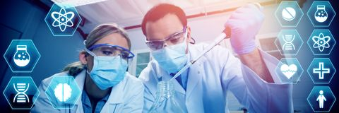 Composite image of medecine. Medecine against science students using pipette to fill test tubes Royalty Free Stock Image