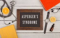 blackboard with text & x22;Asperger& x27;s syndrome& x22;, books, stethoscope, eyeglasses and watch royalty free stock images