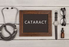 Blackboard with text & x22;Cataract& x22;, stethoscope, eyeglasses and watch. Medecine concept - blackboard with text & x22;Cataract& x22;, stethoscope Royalty Free Stock Photos