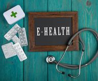Blackboard with text & x22;E-health& x22; and stethoscope on blue wooden background stock image