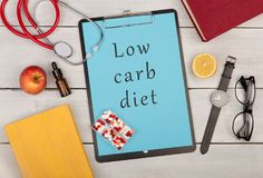 Clipboard with text & x22;Low carb diet& x22;, stethoscope, books, pills, fruits, eyeglasses and watch. Medecine concept - clipboard with text & x22;Low carb royalty free stock photos