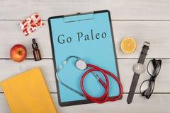 Medecine och att banta begrepp - skrivplattan med text 'går Paleo ', piller, frukter, stetoskopet, bok fotografering för bildbyråer