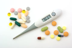 Medecine stuff. Digital thermometer and pills Royalty Free Stock Photos
