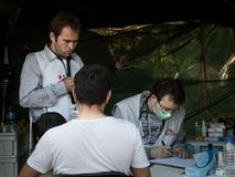 Medecins Sans Frontieres doctors discussing with a refugees family crossing border with Croatia. MSF is an NGO providing doctors. Picture of a doctor from stock photography