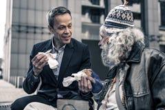 Mededeelzame vriendelijke mens die aan grijs-haired hogere daklozen spreken royalty-vrije stock fotografie