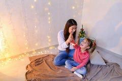 Mededeling van oudere vrouwelijke zuster met jongste meisje die spen Stock Afbeelding