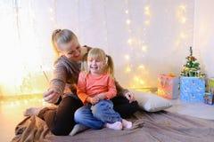 Mededeling van oudere vrouwelijke zuster met jongste meisje die spen Stock Afbeeldingen