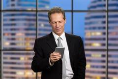 Medelålders affärsman som ser hans smartphone arkivbild