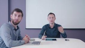 Medelålders affärsman som två sitter i mötesrummet med minnestavlan och bärbara datorn på skrivbordet och diskuterar politely lager videofilmer