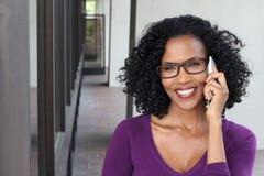 Medelålders afrikansk kvinna som talar på hennes mobiltelefon arkivfoto