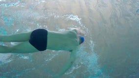 Medelålders caucasian mansimning i vattnet, i simbassängen i Palamos i Spanien lager videofilmer
