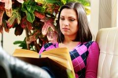 Medelålders härlig kvinna som läser boken Fotografering för Bildbyråer