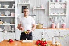 Medelålders idrottsman nen som rymmer en bunke av en platta med en förberedd sallad av gurkan och tomaten Vegetarisk mat Arkivbild