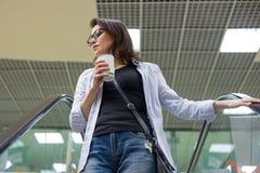 Medelålders kvinna med koppen kaffe, mitt för bakgrundsshoppinggalleriaunderhållning royaltyfri foto