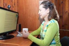 Medelålders kvinna nära hemdatorn Royaltyfria Foton