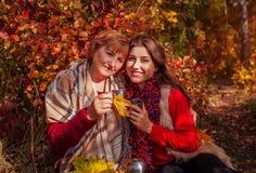 Medelålders kvinna och hennes dotter som har te i skogen fotografering för bildbyråer
