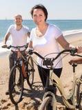 Medelålders kvinna och man med cyklar som går på stranden royaltyfria foton