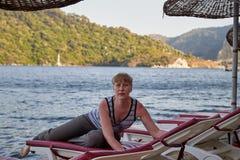 Medelålders kvinna på sunbed av havet och bergen i bakgrunden arkivbilder