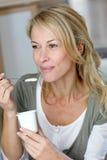 Medelålders kvinna som äter yoghurt arkivfoton
