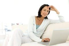 Medelålders kvinna som använder bärbara datorn Arkivfoto