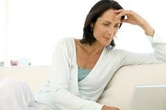 Medelålders kvinna som använder bärbara datorn Royaltyfri Fotografi