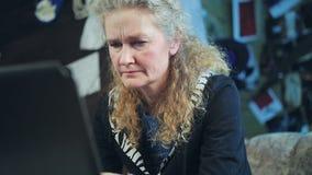 Medelålders kvinna som arbetar på en dator arkivfilmer
