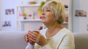 Medelålders kvinna som dricker varmt te av att lugna örter som återställer vattenjämvikt stock video