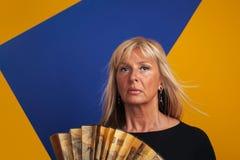 Medelålders kvinna som har en varm exponering som rymmer en fan Royaltyfri Foto