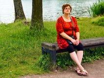 Medelålders kvinna som kopplar av vid sjön Arkivbild