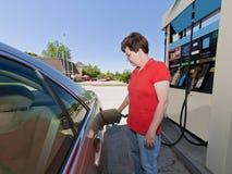 Medelålders kvinna som pumpar bensin Arkivfoto