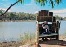 Medelålders kvinna som tar fotografier i fågelrullgardin royaltyfri foto
