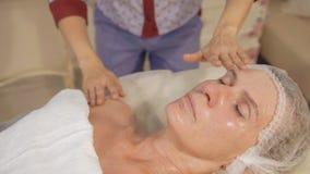 Medelålders lymfatiska tagandeframsida för kvinna och hals, dräneringmassage i brunnsortsalong stock video