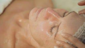 Medelålders lymfatiska tagandeframsida för kvinna och hals, dräneringmassage i brunnsortsalong lager videofilmer