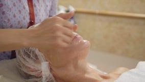 Medelålders lymfatiska tagandeframsida för kvinna och hals, dräneringmassage i brunnsortsalong arkivfilmer