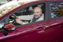 Medelålders man som kör en bil Fotografering för Bildbyråer